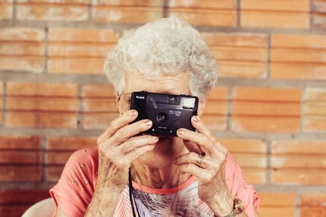 Ældre dame tager billede med et kamera.